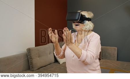 Happy Senior Woman Using Virtual Reality Headset Glasses. Elderly Mature Old Grandmother Rising His