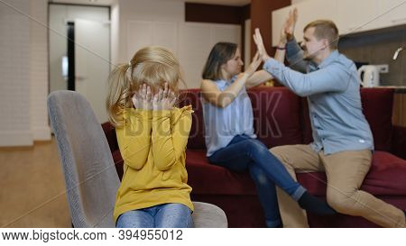 Caucasian Child Girl Kid Is Suffering And Crying From Quarrels Between Parents In Family At Home. An