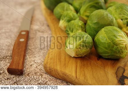 A Pile Of Brussels Sprouts On A Wooden Cutting Board. Organic Brussels Sprouts For Healthy Eating. C