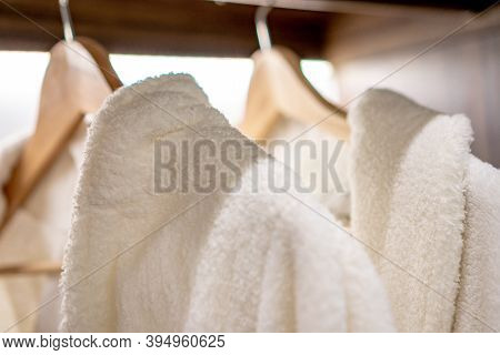White Bathrobes Hung On Wooden Hooks With Balck Bottom In Close Up Concept.