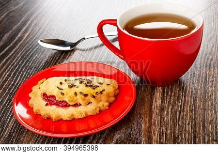 Teaspoon, Shortbread Cookie With Raspberry Jam And Linseeds In Glass Saucer, Red Cup With Tea On Dar