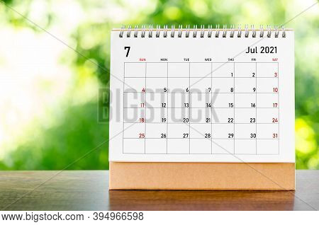 July 2021 Calendar Desk For Organizer To Plan And Reminder On Wooden Table On Nature Background.
