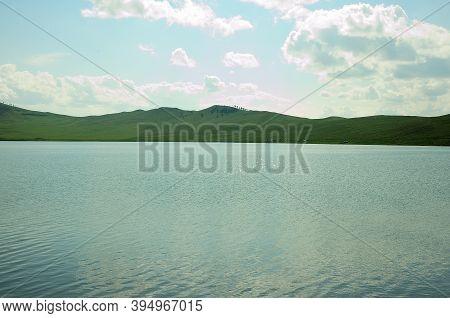 The Surface Of A Calm Blue Lake Surrounded By Tall Green Hills. Lake Matarak, Khakassia, South Siber
