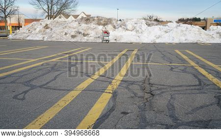 Parking Lots Outside Business Mall With Snow Removed Piles And Single Shopping Cart