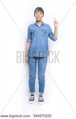 Fashion Full length young woman in jeans shirt and blue jeans showing and pointing up with finger number one isolated on white background