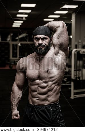 Angry Strong Caucasian Man In Bandana Showing Abdominal And Oblique Muscle In Sport Fitness Gym