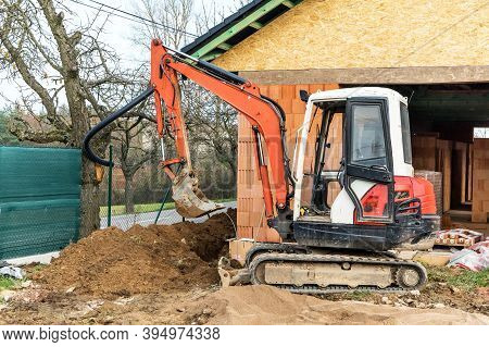 Excavator On Construction Site. Construction Of A Family House. Construction Site With A Small Excav