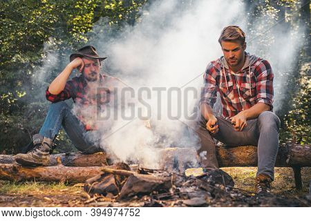 Group Of Friends Enjoying Picnic In The Forest And Drinking Beer. Group Of Two Male Friends Camping