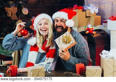 Christmas Couple. Family Happiness Concept. Beautiful Couple Dressed In A Santa Claus Hat. Christmas