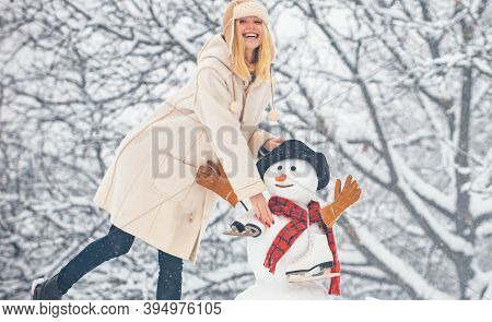 Hipster Girls Friends Playing With Snowman On Snow Winter Landscape. Christmas Preparation - Funny G