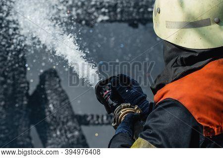 Brave Firefighter Saving Burning Building. Firefighter Work Concept. Firefighter Are Using Water In