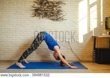 Woman Doing Yoga At Home. Blue Mat And Undershirt. Adho Mukha Svanasana Pose, Sunny Day. Natural Pan