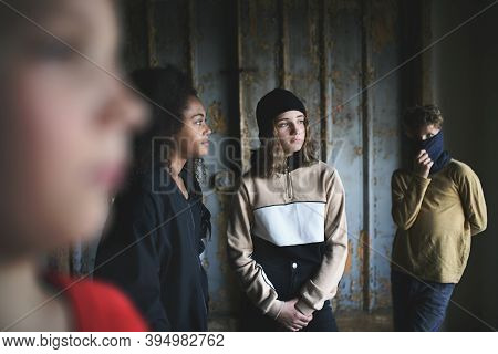 Group Of Teenagers Gang Standing Indoors In Abandoned Building, Bullying Concept.