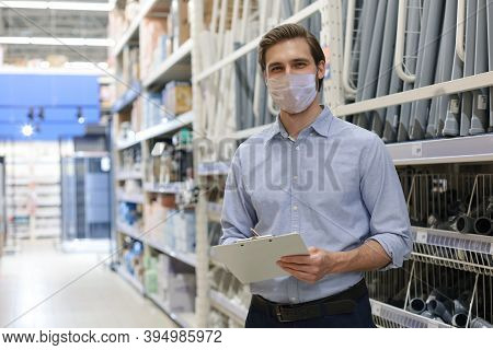 Portrait Of Handsome Warehouse Wears Medical Mask During Epidemy. Worker In A Cash And Carry Wholesa