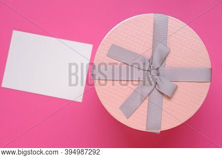 Gift And Postcard For The Holiday.pink Round Box With Bow And Blank Postcard On Pink Background.copy