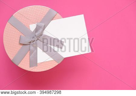Gift And Postcard For The Holiday.pink Round Box With Bow And Blank Postcard On Bright Pink Backgrou