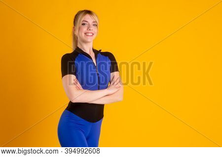 Girl Fitness Trainer In A Blue Jumpsuit On A Yellow Background A Young Athlete Poses And Looks At Th