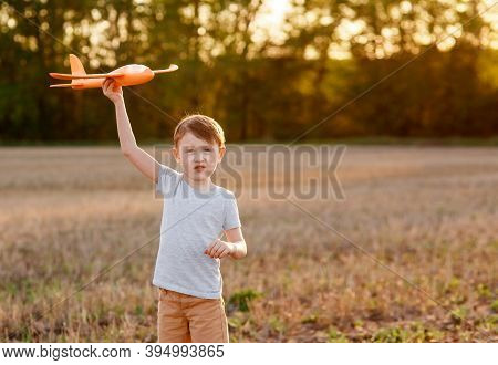 Happy Child Runs With A Toy Airplane On A Sunset Background Over A Field. The Concept Of A Happy Fam