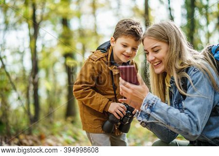 Happy Mother And Son Are Hiking In Forest. They Are Using Maps On Smart Phone.