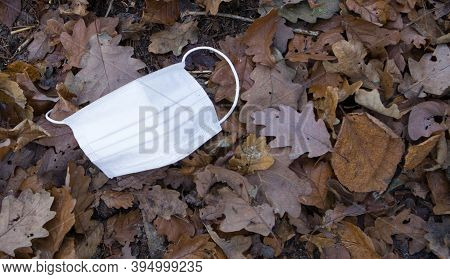 Face Mask On The Ground Covered With Autumn Leaves.top View. Threw Out A Protective Medical Mask In