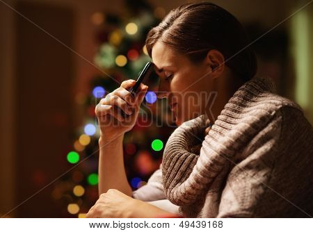 Concerned Young Woman With Mobile Phone In Front Of Christmas Tree