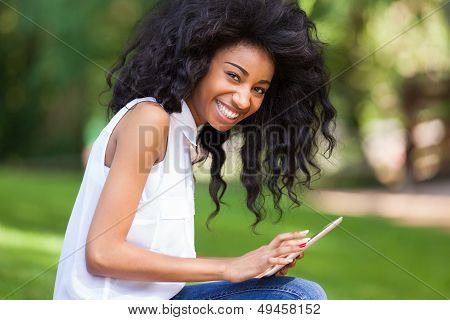 Outdoor Portrait Of A Teenage Black Girl Using A Tactile Tablet - African People