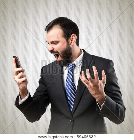 Young Businessmen Shouting To Mobile Over Textured Grey Background.