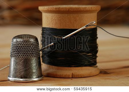 Sewing still life of antique thimble with wooden spool of thread and vintage needle on wood background.  Macro with shallow dof.  Selective focus on thimble and eye of needle.