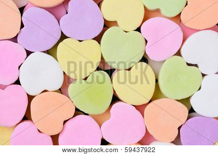 Macro shot of pastel candy hearts for Valentine's Day. The hearts are all bland and ready for your message.
