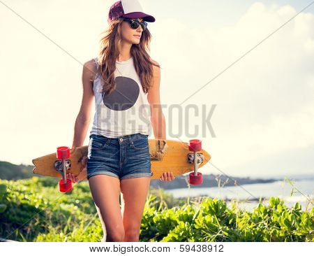 Fashion lifestyle, Beautiful young woman with skateboard, backlit at sunset