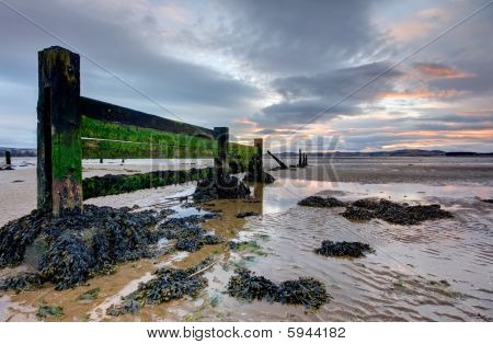 Seaside Groynes During Low Tide At Sunset