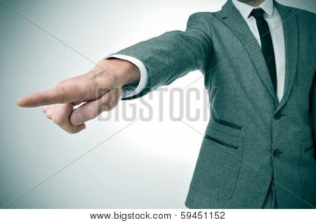 a man wearing a suit pointing with the finger the way out