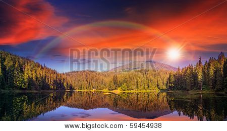 Pine Forest And Lake Near The Mountain Early At Sunset