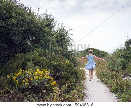 Mature Woman Walking Path To The Beach