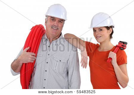 senior craftsman and young craftswoman posing together