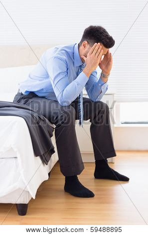 Hungover businessman sitting at edge of bed at home in bedroom