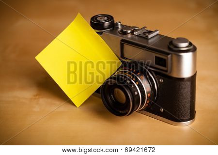 Old photo camera with empty sticky note