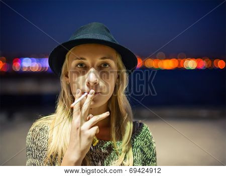 Young Girl In A Hat Smoking A Cigarette On The Street