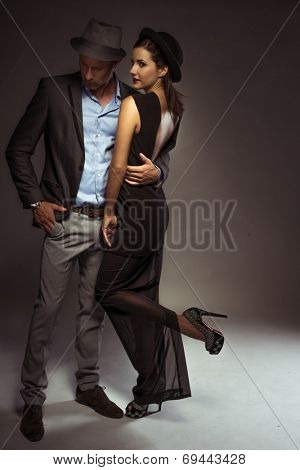 Stylish elegant couple on a date standing in a close embrace in trendy eveningwear with the man looking down and the woman turning to smile seductively at the camera