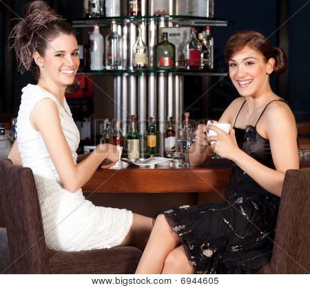 Two Beautiful Young Women Drinking Coffee At Bar