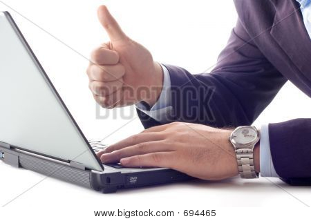 Businessperson ที่ทำงานบนคอมพิวเตอร์ที่มีนิ้วหัวแม่มือของเขาขึ้น