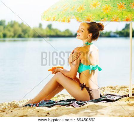 Suntan Lotion Woman Applying Sunscreen Solar Cream. Beautiful happy cute teen Girl applying Sun Tan Cream on her skin on the beach. Sun Tanning. Skin care and Protection. Vacation