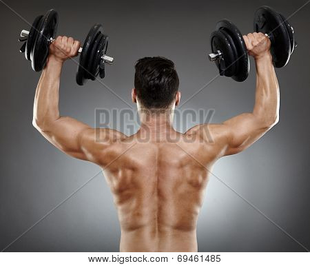 Back of a bodybuilder working with dumbbells for triceps and deltoids poster