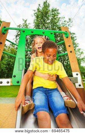 Boy start to slide on chute and girl sit behind