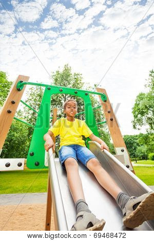 Boys holds sides of chute and sits on it
