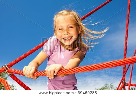 Laughing girl holds rope and stands on it in park