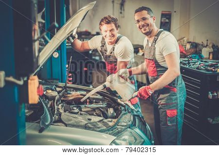 Two mechanics adding oil level in a car workshop