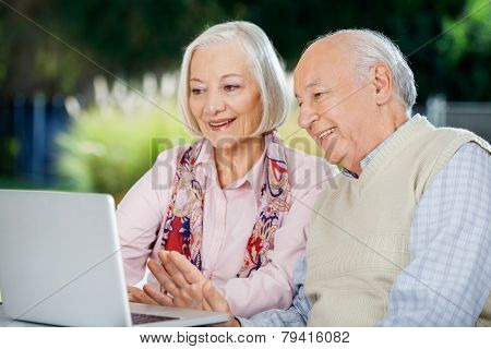Senior couple video chatting on laptop while sitting at nursing home porch