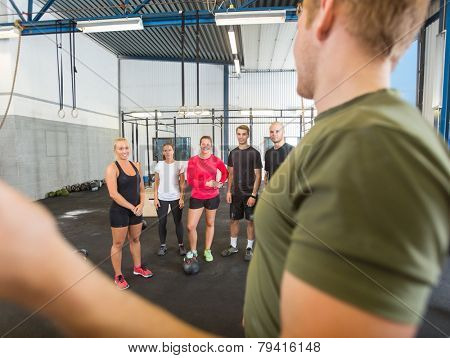 Side view of male instructor training athletes at gym poster