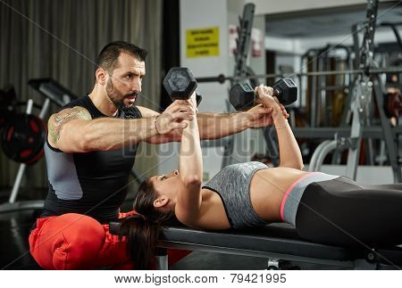 Personal fitness trainer assisting a young woman in the gym at a workout poster